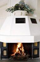 Open fire burning in polygonal, masonry fireplace