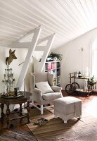 Wing-back chair and footstool, antique table and stuffed deer's head in white, wood-clad attic interior