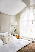 Bed with upholstered headboard and fabric canopy in front of arched window