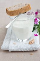 Glass of milk and shortbread with scented geranium oil