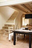 Black wooden table and simple kitchen chairs in front of stone and wood staircase in open-plan, rustic interior with wood-beamed ceiling