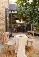 Pale grey kitchen chairs and table with tablecloth on terrace below lemon tree in front of open terrace doors with view of dining area
