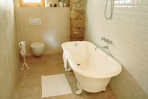 Free-standing, retro bathtub and toilet in bathroom of Spanish stone house
