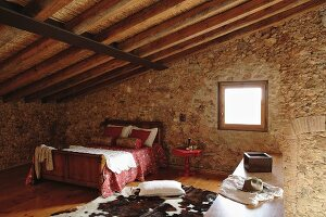 Double bed under sloping roof of Spanish stone house