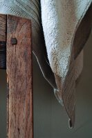 Towel in elegant natural fabrics next to wooden chair back