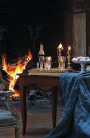 Champagne glasses and bottle on tray next to dish and draped tablecloth on simple wooden table in front of open fire