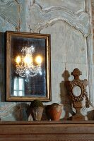 Gilt-framed mirror on faded wood-panelled wall and terracotta pots next to wooden sculpture on table top