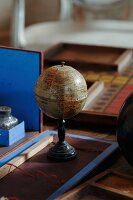 Stylised, vintage globe with stand on desk