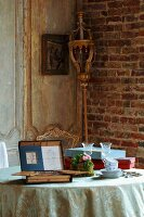 Breakfast crockery next to open box of painting utensils on table and processional staff in corner of rustic room
