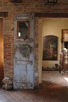 Decorative old wooden door against brick wall in rustic hallway of French country house; antique oil painting in background