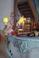 Collection of antique flea-market finds and small lit lamps on Rococo console table; mirror reflecting staircase in background