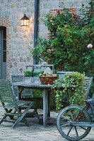 Terrace seating area with faded wooden furniture in front of climber-covered facade of old, French stone house
