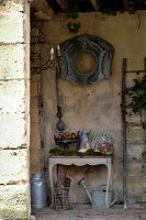 Arrangement of antique flea-market finds in roofed store area of old, French country house