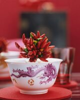 A bundle of chilli peppers in a porcelain bowl with a dragon motif