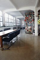 Conference table on castors and tall bookcase in bright, spacious loft interior with industrial windows