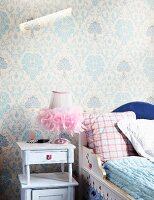 Painted wooden child's bed against wallpaper with traditional pattern and next to lamp with tulle lampshade on romantic vintage bedside table