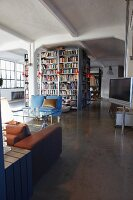 Open-plan loft apartment with light blue upholstered sofa in front of large complex of bookcases and flat-screen TV mounted on floor-to-ceiling pole to the right