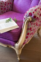 Book on reading chair with gilt wooden frame and colourful, spotted modern upholstery