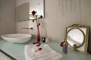 Toiletries on designer washstand with counter-top basin on glass counter and flower in vase next to vintage mirror