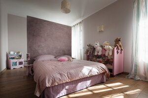 Double bed against lilac partition and soft toys on half-height shelving in modern bedroom