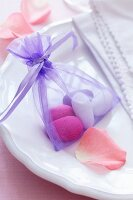 Sugared almonds in small satin bag as wedding favour