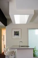 Shaft-shaped skylight above a kitchen island clad with stainless steel and a row of white bar stools