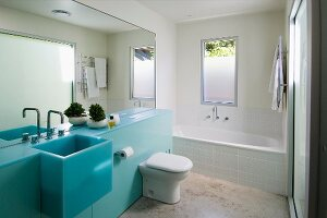 Designer bathroom with full mirror wall above a bright blue vanity with a trough sink