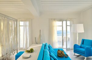 Mediterranean bedroom with blue upholstered furniture, table and stool in lounge area next to four-poster bed