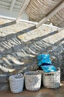 Stacked blue towels in one of three wicker baskets standing against stone wall on roofed terrace