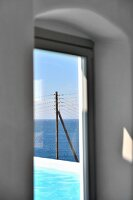 View of pool and electricity pylon in front of open sea through window