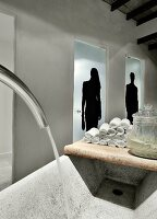Towels on vintage wooden board next to rustic stone trough in front of glass doors with silhouette motifs of a man and a woman