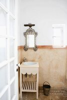 Moroccan bathroom in soft earthy shades with ornate mirror, wooden washstand, half-height marbled wall and terracotta floor