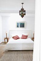 Simple bed with wood-panelled headboard and bright scatter cushions below Oriental pendant lamp