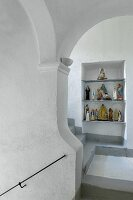 Religious figurines in niche in white stairwell with grey treads