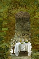 Secluded dining area in stone vaulted room with old church pew