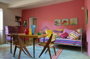 50s-style dining table and wooden chairs with wicker seats in front of daybed with striped cushions against pink-painted wall