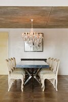 Table and vintage-style, pale chairs below chandelier hanging from exposed concrete ceiling