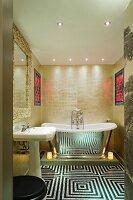 Extravagant bathroom with op art floor in front of mirrored, vintage bathtub