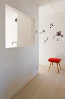 Stool with red pad in a simple, minimalist lobby and pass through in a wall with a view of a kitchen faucet
