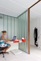Lady at a modern desk in an open corner with glass walls and a view of a wardrobe in the hallway