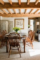 Country-house-style dining room with tasteful wooden furniture below wood-beamed ceiling; floral screen in corner