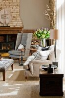 Wood-burning stove in open fireplace with brick chimney breast behind checked grey reading chair; magnificent summer bouquet in corner