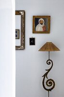 Standard lamp with curved metal base and lampshade below framed pictures on wall