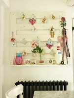Wall-mounted peg board hung with various decorative objects above radiator in kitchen