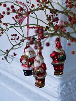 Father Christmas baubles hanging on branches of red berries