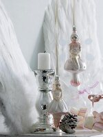 Angel Christmas tree baubles next to chrome candlestick in front of decorative angels' wings leaning on wall