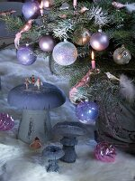 Christmas tree decorated with baubles and lit candles next to mushroom ornaments on animal-skin rug