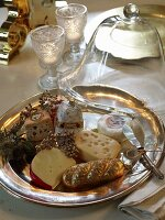 Platter of various cheese-shaped ornaments under half-open glass cheese cover