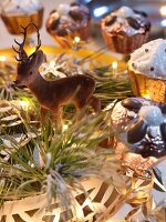 Deer figurine and cake-shaped ornaments in dish with fairy lights