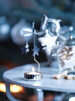 Tealight carousel with lit candle next to storage jar of festive biscuits on side table